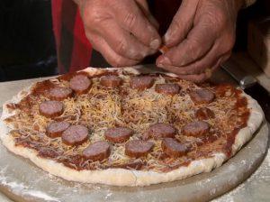 Guy places kielbasa on pizza.