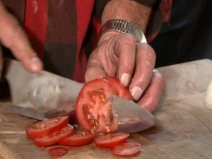 Guy slices a tomato with a Rada French Chef knife.