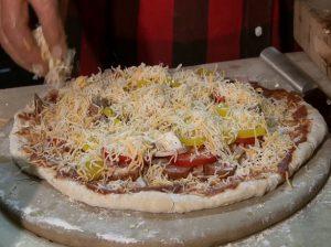 Guy prepares to bake a kielbasa pizza.