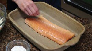 Kristi seasons a batch of fish in a Rada Rectangular Baker.