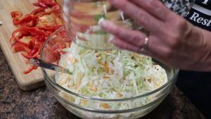 Kristi adds vegetables to slaw.