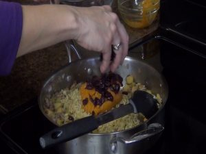 Jess adds raisins to pot.
