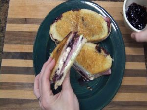 A completed sourdough ham cranberry sauce sandwich.