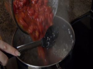 Jess places tomatoes in a pan with a Rada Non-Scratch Spoon.