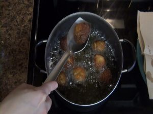 Dough balls are lifted out of oil.