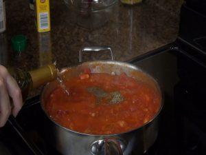 Jess adds white wine to tomato sauce.