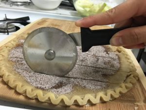 Kristin cuts crust with a Rada Pizza Cutter.