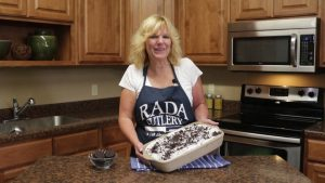 Kristi poses with a completed Oreo Poke Cake in a Rada Rectangular Baker stoneware pan.