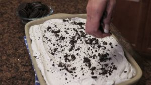 Kristi places crushed Oreo cookies on top of a cake topping.