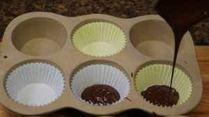 Chocolate is poured into cupcake liners.