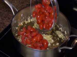 Tomatoes are added to a saucepan.