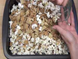 Chex cereal is added to popcorn.