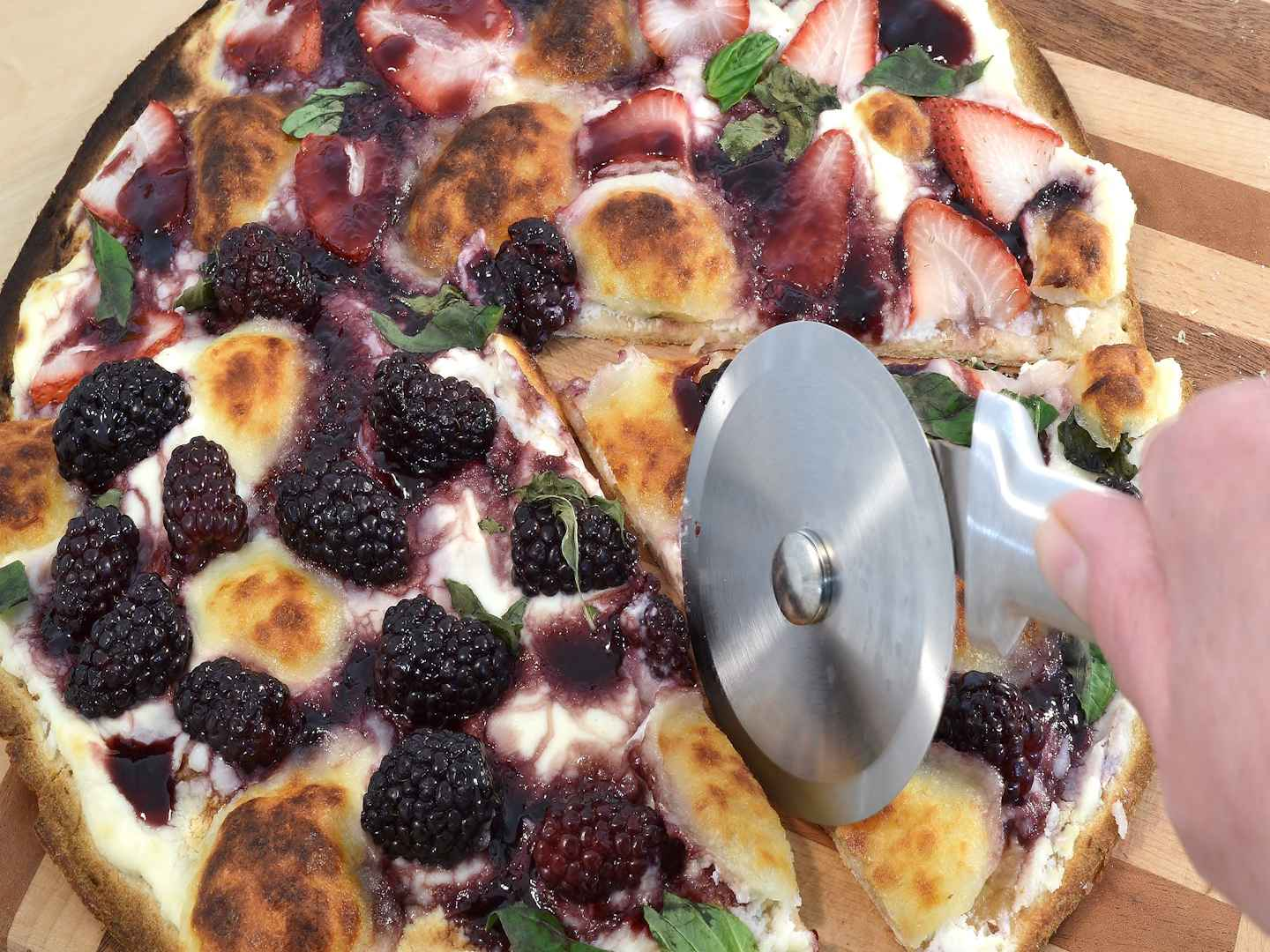 A delicious Blueberry Ricotta Pizza being cut but a Rada Pizza Cutter.