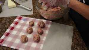 Ground beef is rolled into balls.