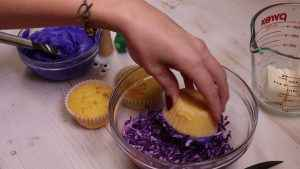 A cupcake is dipped in purple coconut flakes.