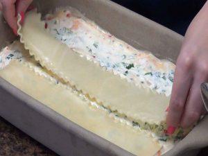 Jess places lasagna noodles on mixture.