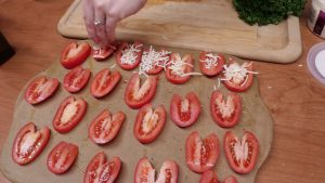 Jess adds Asiago cheese to tomatoes.
