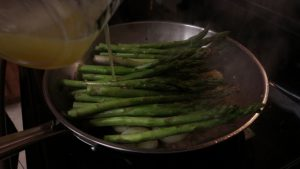 Jess adds broth to asparagus.
