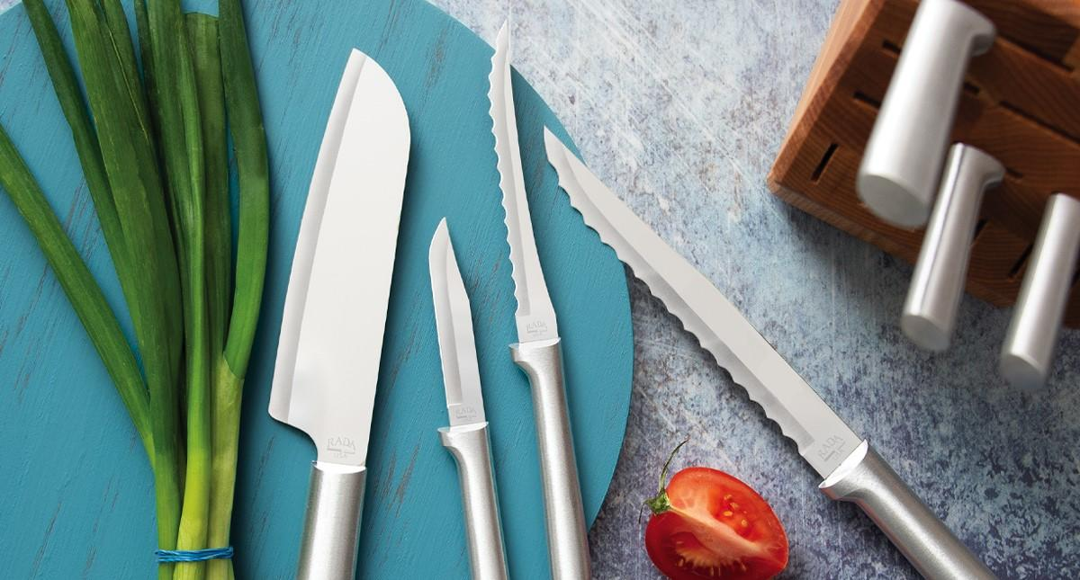 Four Rada Cutlery knives on a blue plate with chives and a tomato next to the Rada Oak Block