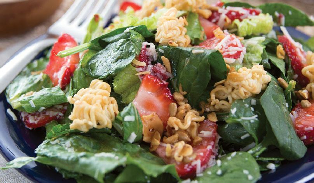 Salad with strawberries and uncooked noodles on a blue plate with a fork